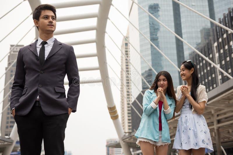 Les filles asiatiques regardent l'homme d'affaires bel photos stock