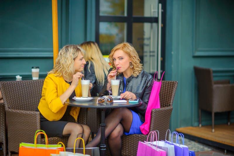 Les filles avec des sacs à provisions s'asseyent à une table dans un café, un café de boissons et un sourire images libres de droits
