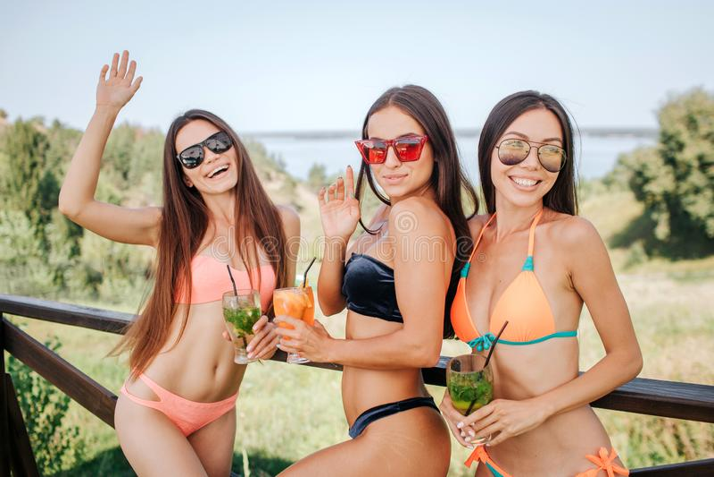 Les filles bien baties et magnifiques se tiennent et posent sur l'appareil-photo Ils verres de prises avec des cocktails Les jeun photographie stock