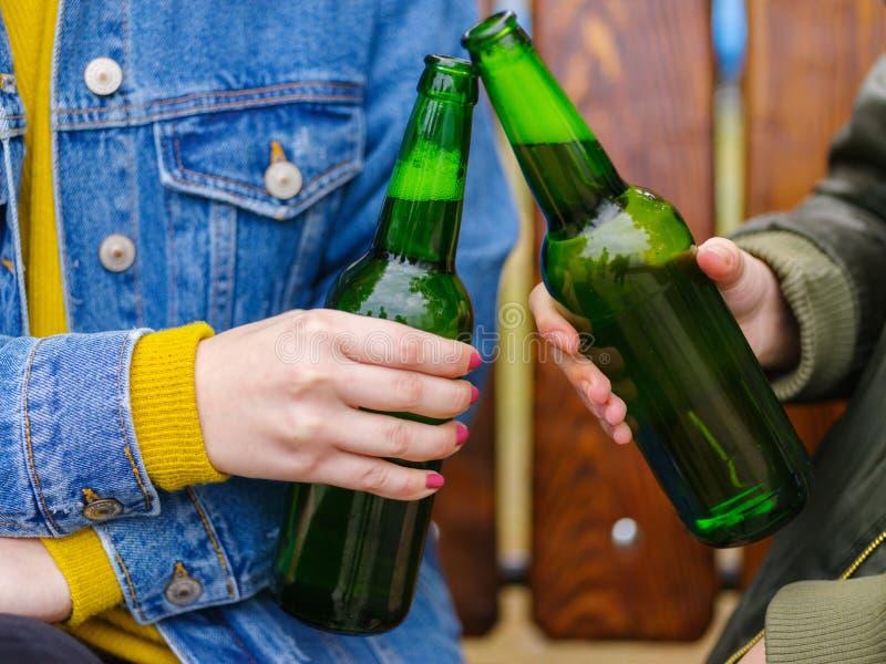 Les filles boivent de la bière sur un banc dans la rue photos libres de droits