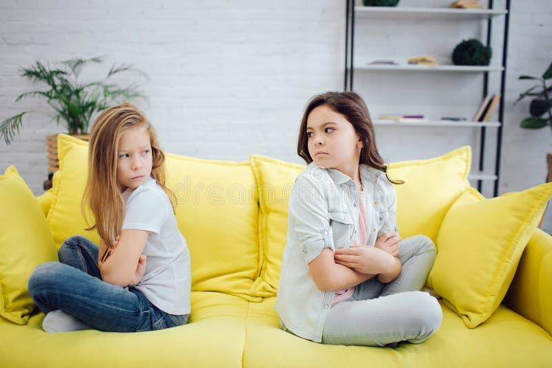 Les filles contrariées et fâchées s'asseyent sur le sofa jaune et le regard à l'eah autre Ils jugent des mains croisées Les adole image libre de droits