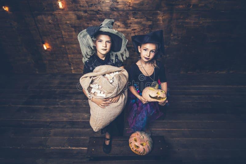 Les filles d'enfants costume des sorcières avec des potirons et des festins dans photos libres de droits