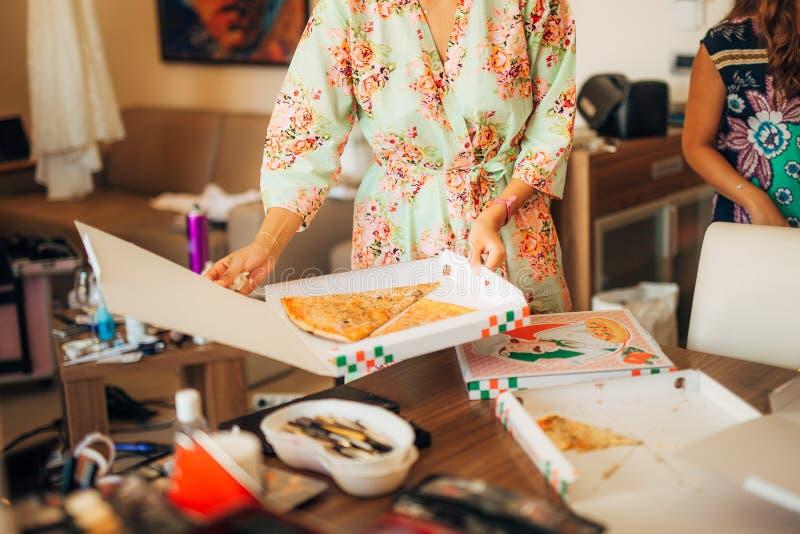 Les filles dans des robes de chambre ont commandé la pizza photos stock