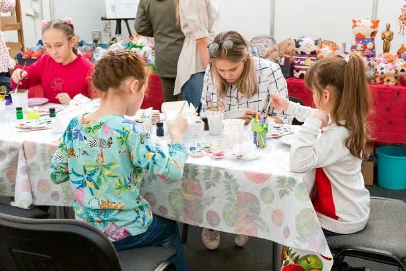Les filles dessinent sous la direction d'un professeur à la table dans la salle d'enfants à la foire traditionnelle populaire des photographie stock libre de droits