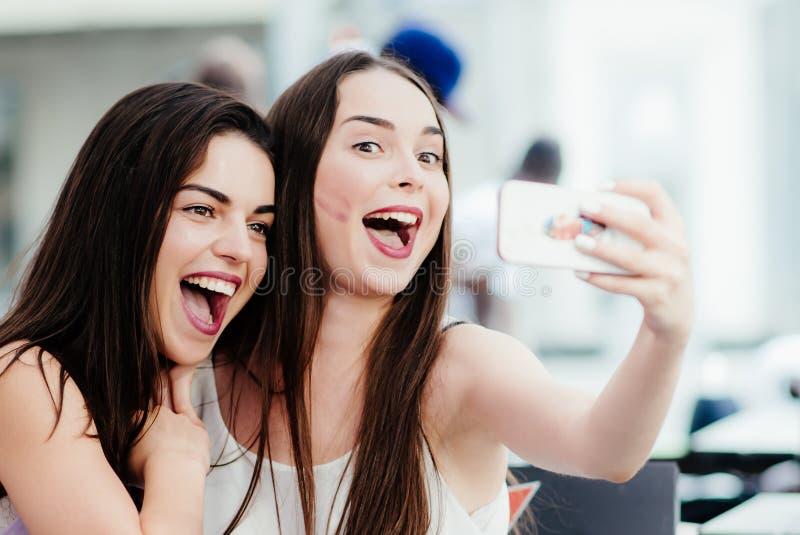 Les filles font un repos en café et font des selfies images libres de droits