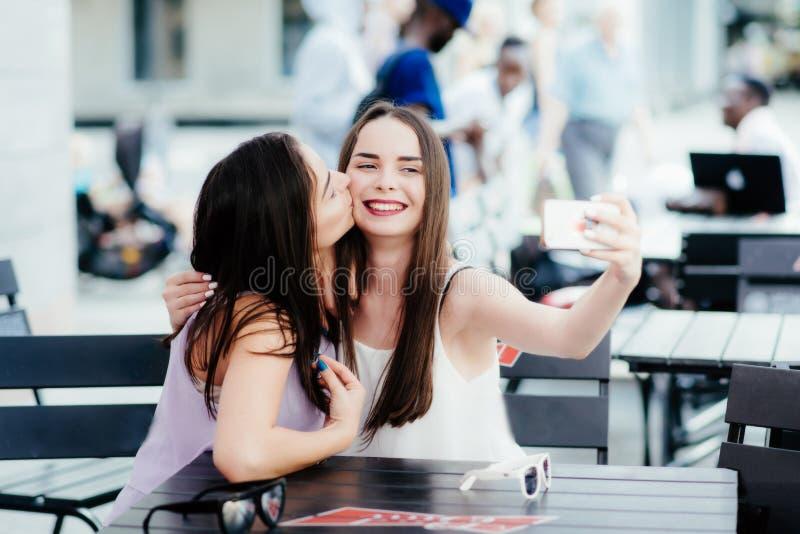 Les filles font un repos en café et font des selfies photographie stock libre de droits