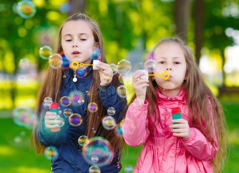 Les filles jouent avec des bulles de savon dans un printemps photos libres de droits