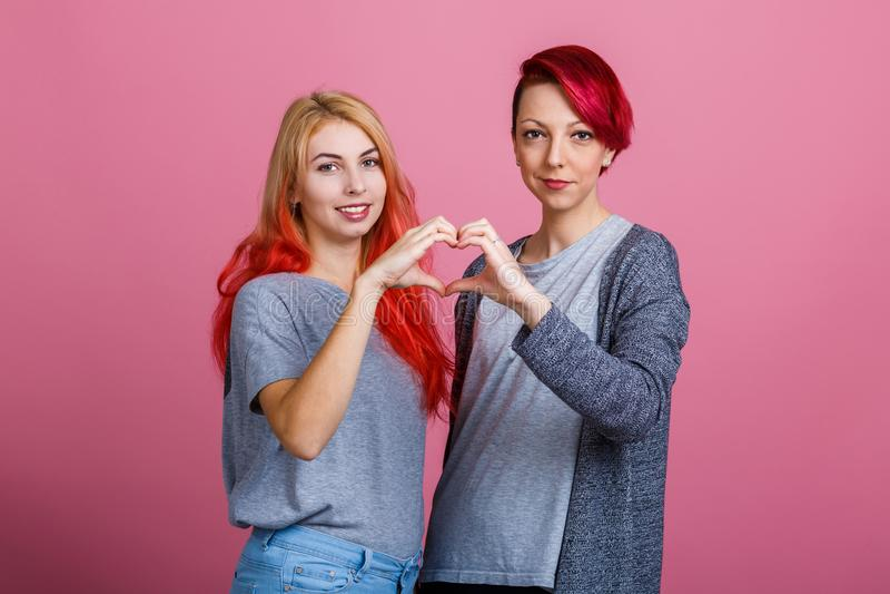 Les filles ont joint des mains et ont fait un coeur sur un fond rose image libre de droits