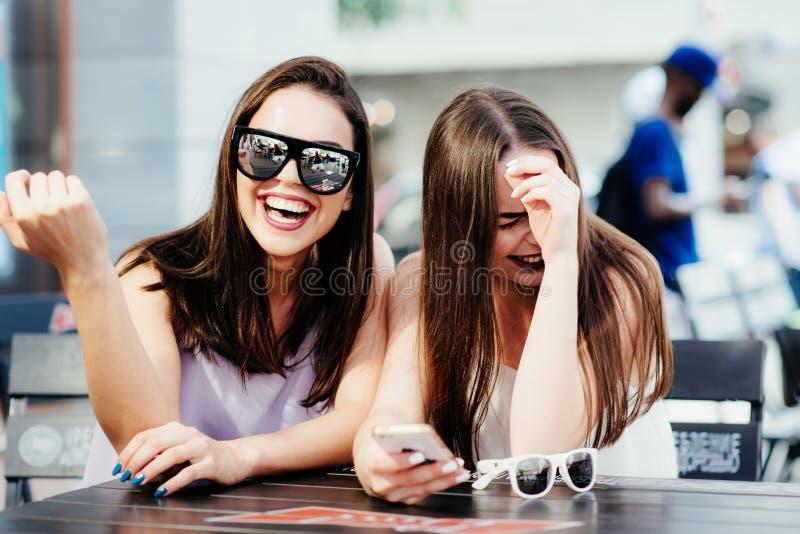 Les filles ont l'amusement avec un téléphone en café image libre de droits