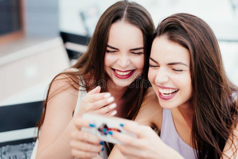 Les filles ont l'amusement avec un téléphone en café photo stock