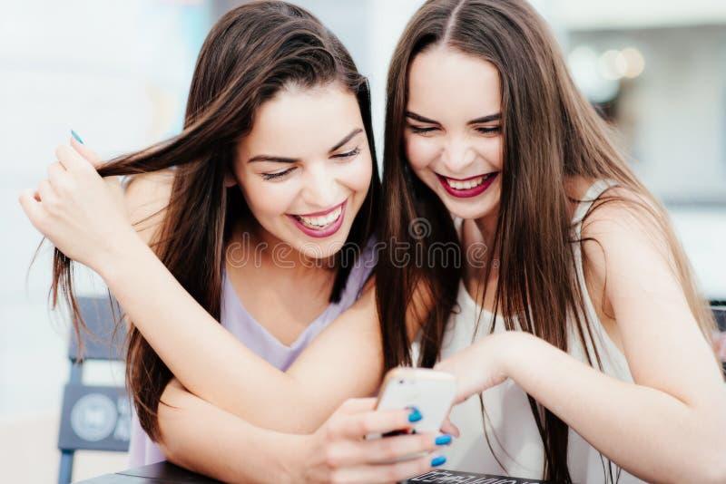 Les filles ont l'amusement avec un téléphone en café photos libres de droits