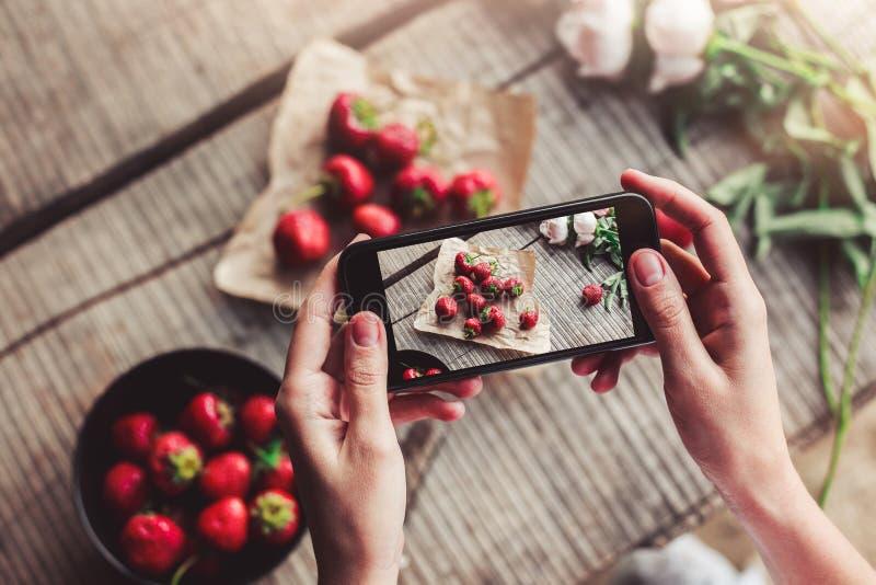 Les filles remet prendre la photo du petit déjeuner avec des fraises par le smartphone photo libre de droits