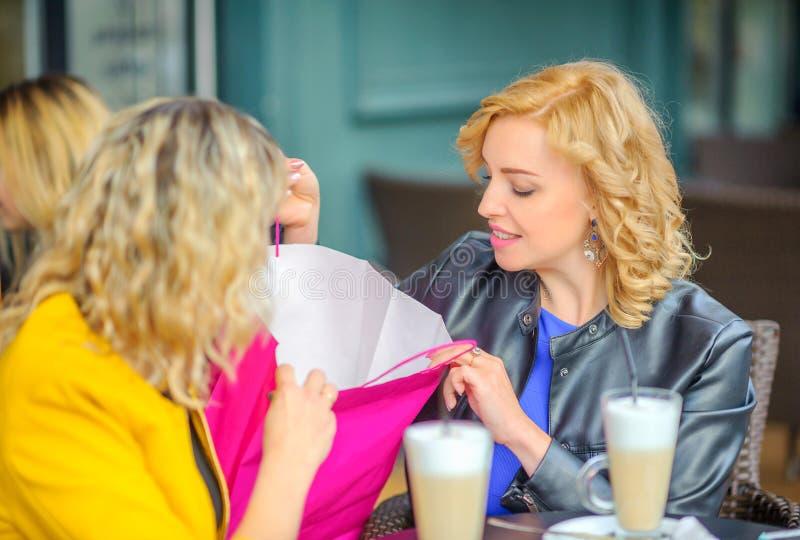 Les filles s'asseyent à une table dans un café extérieur photos libres de droits