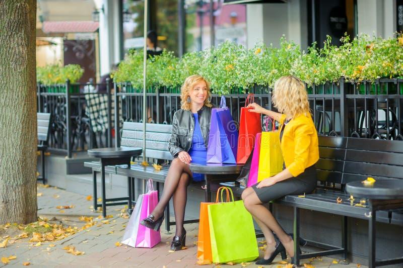 Les filles s'asseyent à une table dans un café extérieur avec des paquets d'achats photos libres de droits
