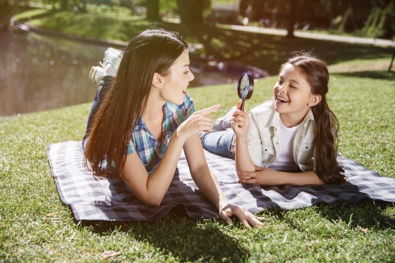 Les filles se trouvent sur la couverture et regardent l'un l'autre Ils jouent avec la boucle La mère le tient et le regarde photographie stock libre de droits