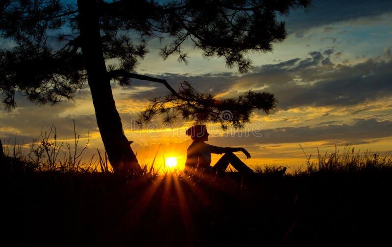 Les filles silhouettent dans le reflexia de méditation au coucher du soleil photo libre de droits