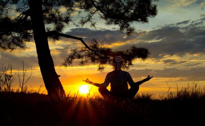 Les filles silhouettent dans le reflexia de méditation au coucher du soleil image libre de droits