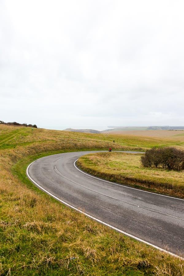 Les flammes vides ondulent la route de manque dans les domaines verts avec le ciel nuageux o photo stock