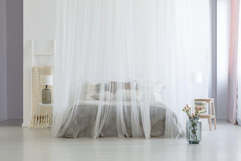 Les fleurs à côté de l'auvent enfoncent dans l'intérieur lumineux blanc de chambre à coucher avec photos stock