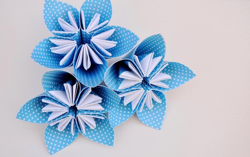 Les fleurs bleues d'origami faites en polka ont pointillé le papier photos stock