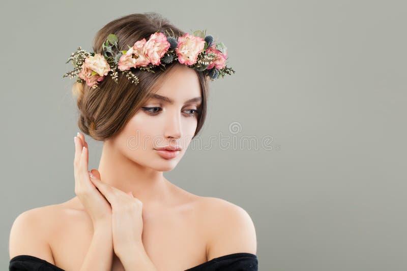 Les fleurs de port de jolie jeune femme tressent sur le fond gris de bannière images stock