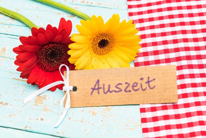 Les fleurs et la carte cadeaux colorées avec le mot allemand, Auszeit, temps mort de moyens ou détendent image stock