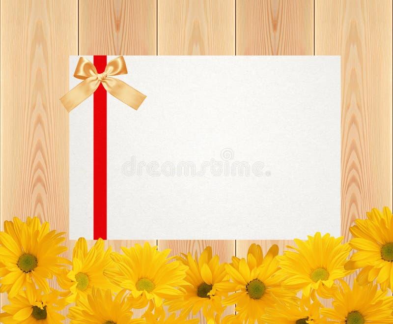 Les fleurs et la carte jaunes de chrysanthème sur les planches en bois donnent à c une consistance rugueuse illustration stock