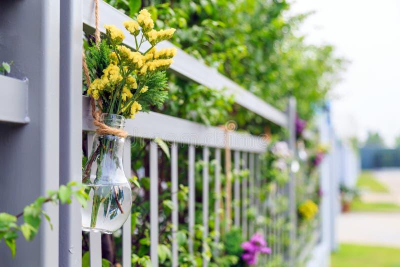 Les fleurs jaunes dans l'ampoule ont formé le vase accrochant sur la barrière à la maison photographie stock libre de droits