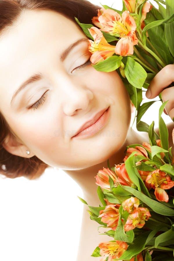Les fleurs rose-jaunes lumineuses de fith de jeune femme se ferment  photos stock
