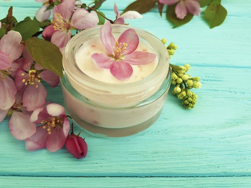 Les fleurs roses cosmétiques crèmes sur le bois en bon état frottent, fait main image libre de droits