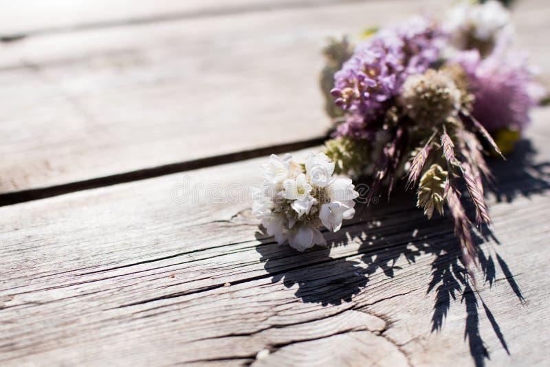 Les fleurs sauvages de champ ont recueilli dans un petit groupe et sur une étiquette en bois photo stock