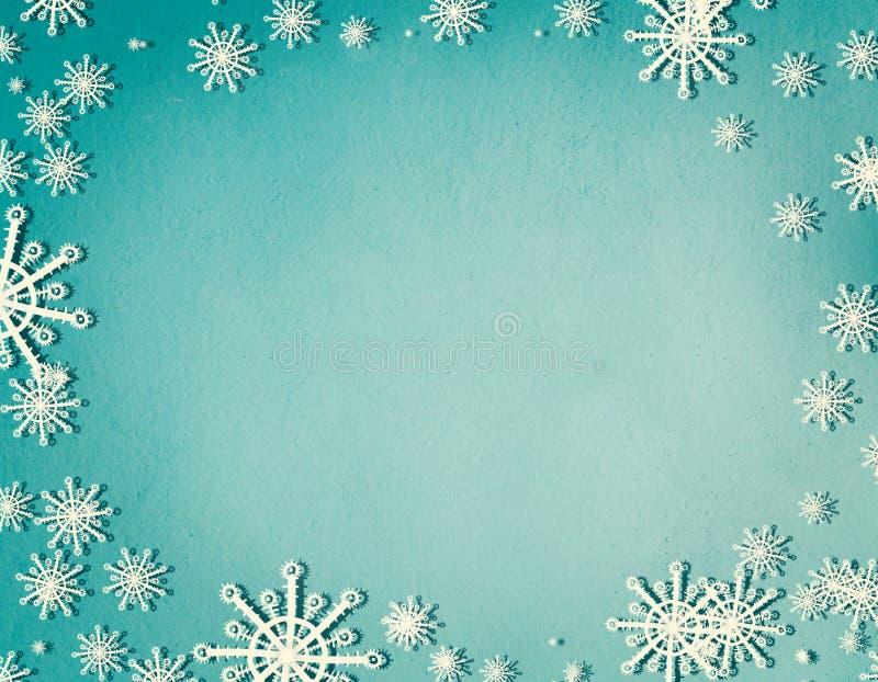 Les flocons de neige encadrent sur le fond bleu de turquoise avec l'espace de copie, vue supérieure Concept de vacances de Noël e image stock