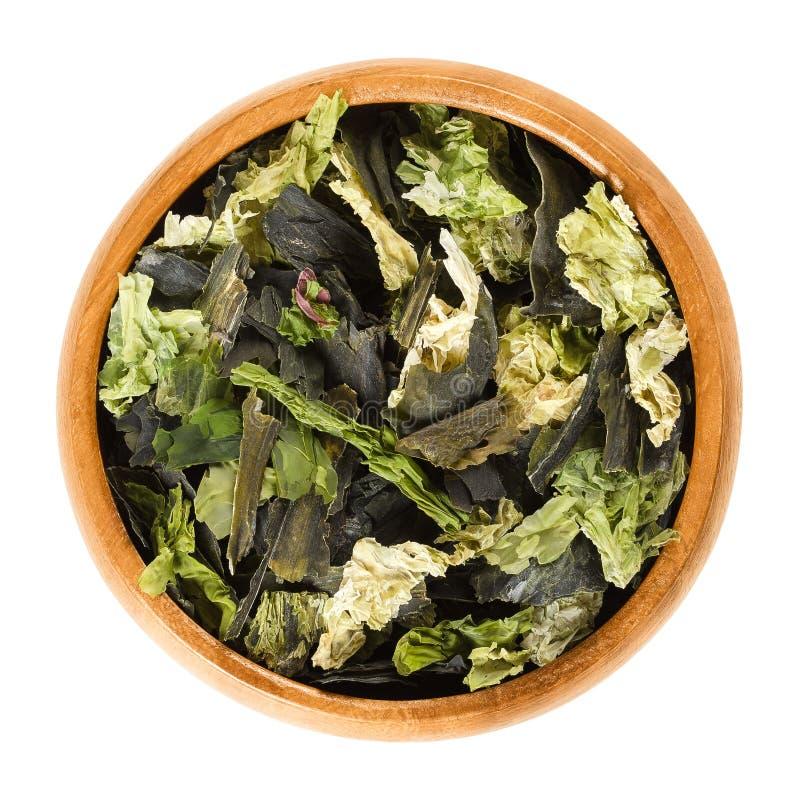 Les flocons secs d'algues se mélangent dans la cuvette en bois au-dessus du blanc photographie stock