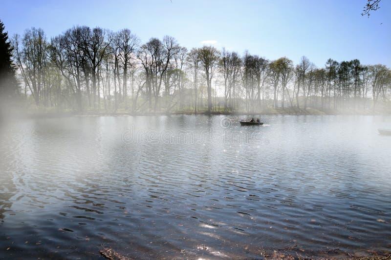 Les flotteurs de bateau sur la rivière par le brouillard tôt le matin avec deux personnes image libre de droits