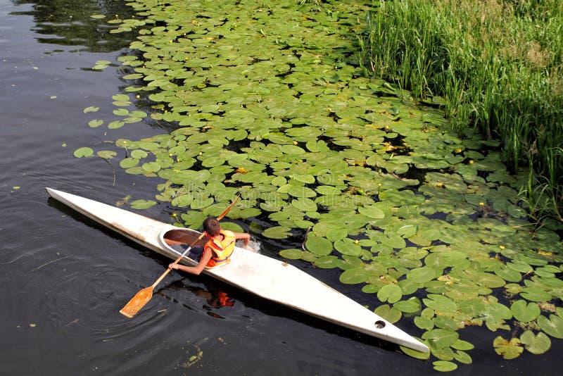 Les flotteurs de garçon sur le kayak en bas de la rivière photographie stock libre de droits