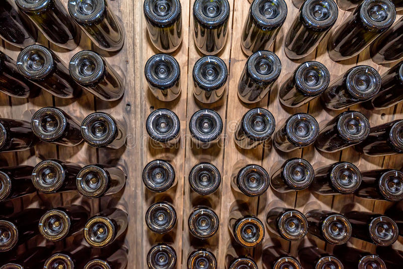 Les fonds des bouteilles de vin empilées dans la cave image stock
