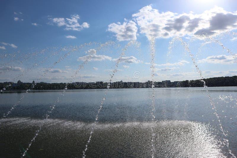 Les fontaines sur le lac dans la ville se garent images libres de droits