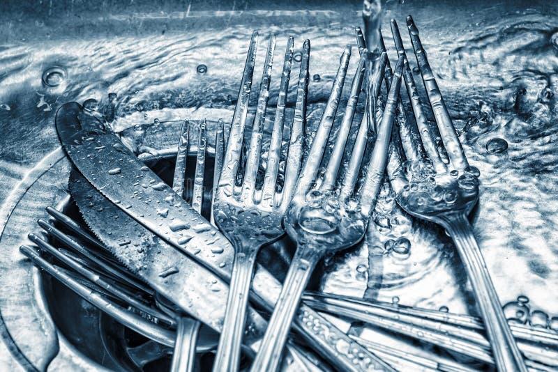 Les fourchettes et les couteaux ont lavé sur un évier de cuisine images libres de droits