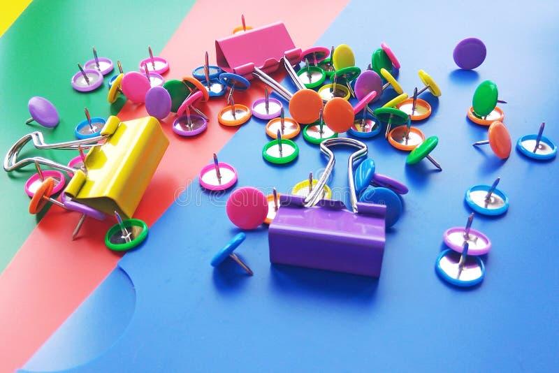 Les fournitures de bureau d'école et les trombones, goupilles sur le fond coloré de dossiers photo stock