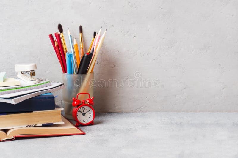 Les fournitures scolaires, carnets de livres crayonnent sur le fond gris avec l'espace de copie photos stock
