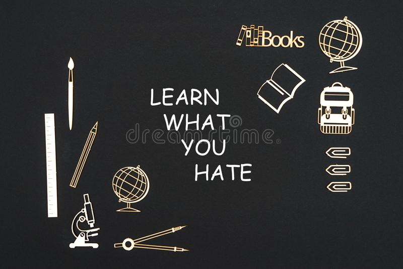Les fournitures scolaires placées sur le fond noir avec le texte apprennent ce que vous détestez illustration stock