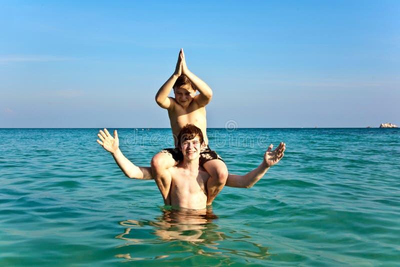 Les frères apprécient l'eau chaude claire au beau beac photographie stock libre de droits