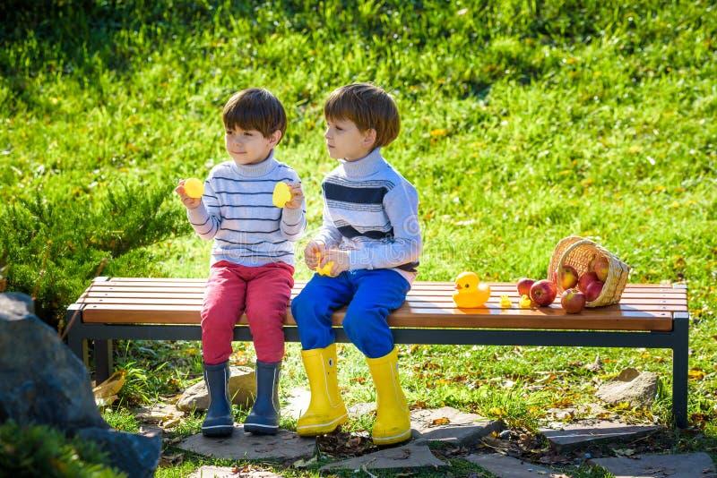 Les frères de petits enfants s'asseyant sur le banc en bois jouent avec le caoutchouc du images stock