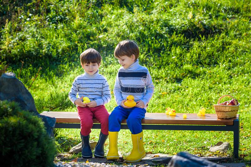 Les frères de petits enfants s'asseyant sur le banc en bois jouent avec le caoutchouc du image libre de droits