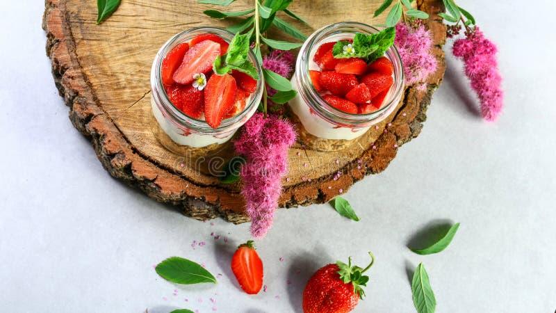 Les fraises abandonnent avec de la crème et des céréales servies sur les tasses en verre plus de sur un tronçon en bois Image aut photographie stock libre de droits