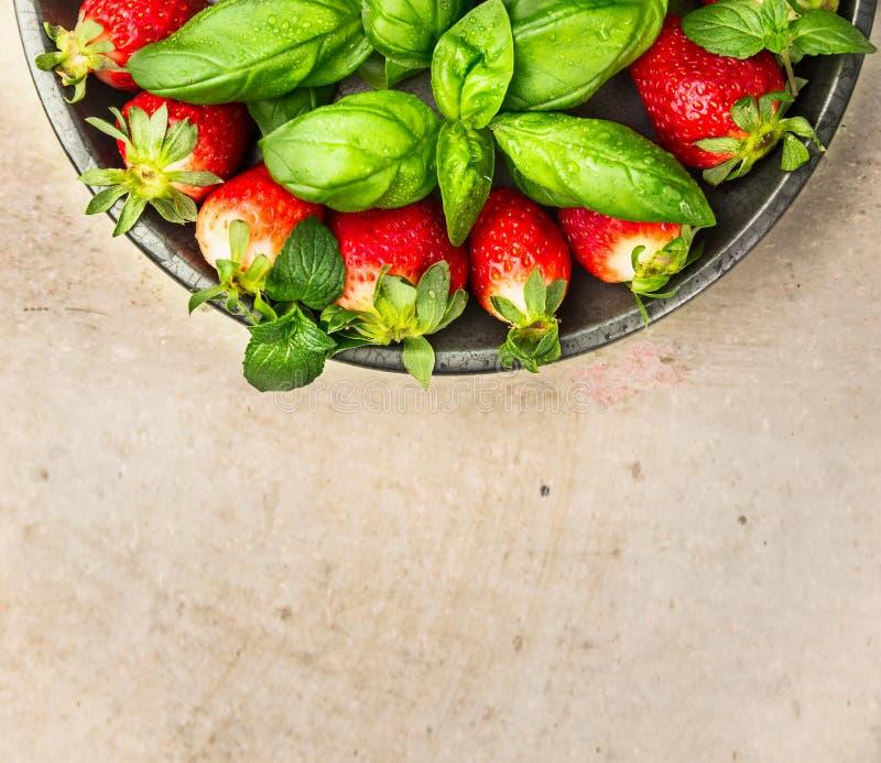 Les fraises avec le basilic part dans le plat gris sur la table beige, vue supérieure, fin  image stock
