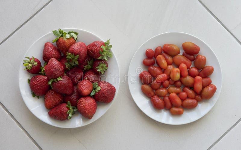 Les fraises fraîches et les petites tomates fraîches ont servi d'un plat blanc et à l'arrière-plan en céramique naturel gris Frui images libres de droits