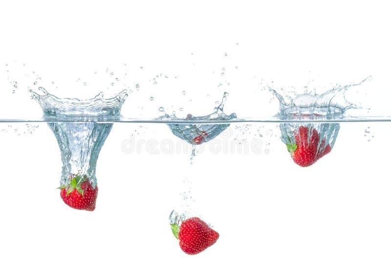 Les fraises tombant dans l'eau avec éclabousse photos stock