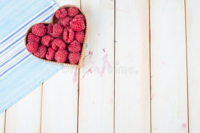 Les framboises fraîches au coeur forment le panier sur la cuisine photos stock