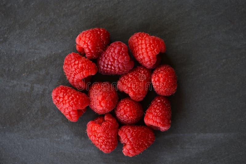 Les framboises fraîches portent des fruits vue supérieure de fond foncé photo libre de droits